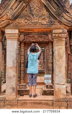 SIEM REAP, CAMBODIA - MARCH 10, 2009: Tourist at Banteay Srei, a 10th century Hindu temple dedicated to Shiva. The temple was forgotten for centuries and rediscovered 1814.
