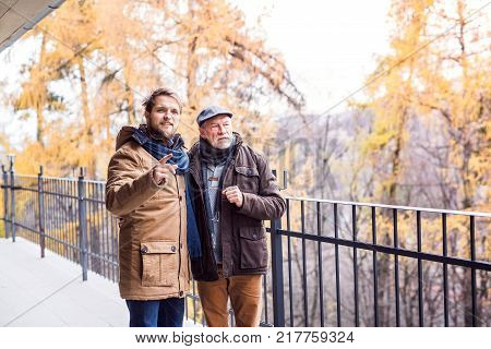 Senior father and his young son on a walk in town.