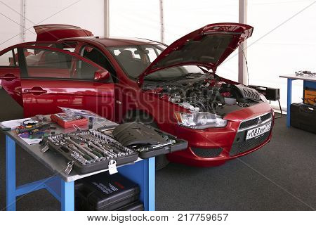 MOSCOW, AUG. 22, 2017: View on clean working place for car diagnostics and maintenance repair with new electronic equipment and hand tools. Car engine diagnostics maintenance station. Car open hood