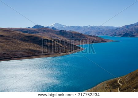 Panoramic view of Tibet natural landscape - blue azure water lake surrounded desert mountains. Yamdrok Lake (Yamdrok Yumtso Yamzho Yumco) is a sacred lake in Tibet.