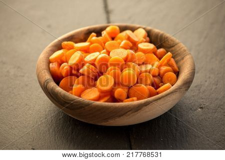 Carrot slices in wooden bowl. Fresh cut crisp slivers of Daucus carota, a root vegetable with orange color. Edible taproot pieces. Isolated macro food photo close up from above