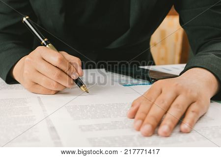 Close up businesswoman signature terms and conditions document paper on working space, business signing concept