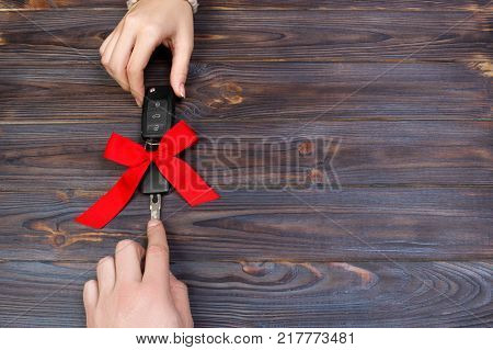 Woomen give car key. Woman hand hold car key with red bow. Giving a car as a gift.