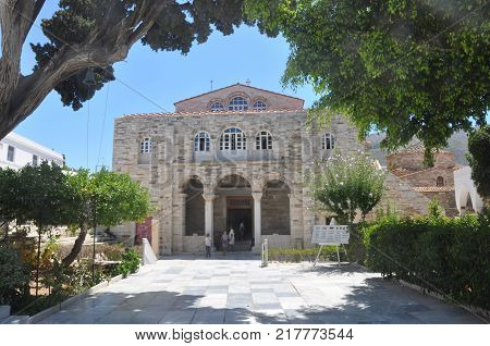 Church of Panagia Ekatontapiliani in Parikia, typical front entrance view with tree branches in sunny day with a few blurry unrecognizable tourist, Paros island, Cyclades, Greece