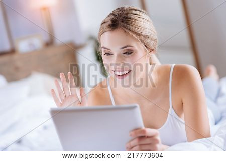 Hello there. Upbeat pretty woman lying on the bed and making a video call via tablet while waving at the front camera