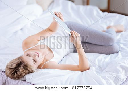 Interesting articles. Beautiful slender woman lying on the bed and reading news online, using her tablet