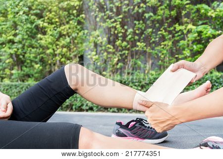 Young woman runner ankle being applied bandage by man in park. injury ankle