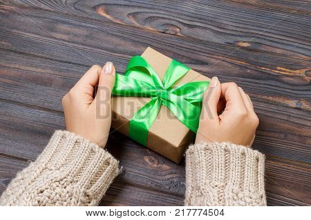 Gift or present with green bow. Woman hands showing and giving gifts. Closeup of present made of recycled carton and green ribbon on wooden background.