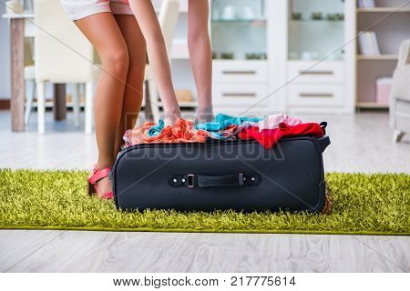 Woman trying to fit all clothing to suitacase before vacation