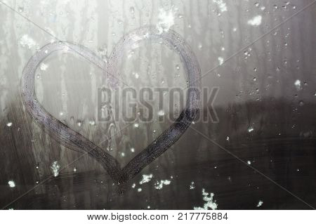 Sticky snow on a hand-drawn heart on the sweaty glass