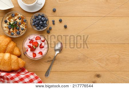 Rich continental breakfast background. French crusty croissants, muesli, yogurt, sweet berries and hot coffee for tasty morning meals. Delicious start of the day. Top view, copy space on natural wood