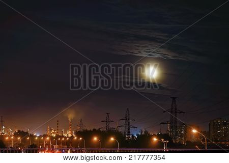 Industrial district of the city at night. Residential houses and industrial pipe, power lines. Ecology, atmosphere, pollution of environment. Full moon on a cloudy night. Blurred background