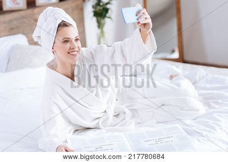 Capturing perfect moment. Beautiful young woman lying on the bed, reading a newspaper and taking a selfie while wearing a towel turban and a bathrobe