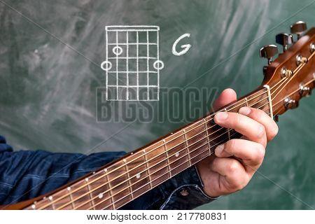 Man in a blue denim shirt playing guitar chords displayed on a blackboard, Chord G