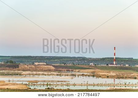 Natural lake is a chalky quarry with a factory smokestack under a green hill on the horizon. Technogenic industrial landscape.