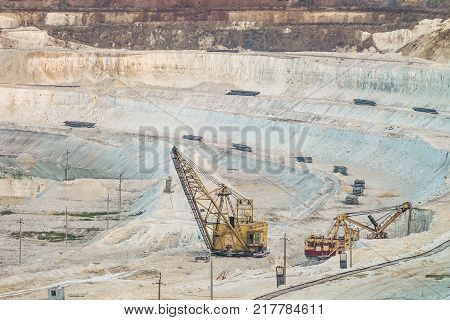 Work of heavy grapple excavators in a deep chalk quarry. Mining industry. Big clamshell excavators in the lowland quarry.