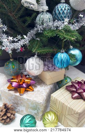 A morning surprise under a Christmas tree. Three light gift boxes with colorful bows under decorated Christmas tree. Blue and white glitter ornaments and tinsel hanging on a fir tree.Christmas or New Year background.