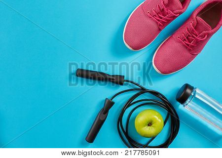 Flat lay of female sport equipments, jump rope, bottle of water and pink sneakers on blue background. Sports and healthy lifestyle concept. Top view. Copy space. Still life