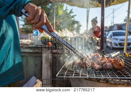 Lao street vendor frying meat on grill in Vientian, Laos