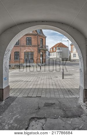 One of the many quaint little buildings in the old town of Helsingor in Denmark as seen through an archway.