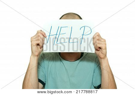 Young depressed man suffering from anxiety and feeling miserable holding help sign on paper in his hands and leaning on the white wall partially isolated