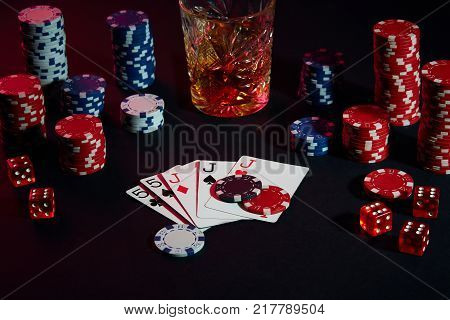 Cards of poker player. On the table are chips and a glass of cocktail with whiskey. Still life. The concept of gambling. Poker Online. Combination of cards