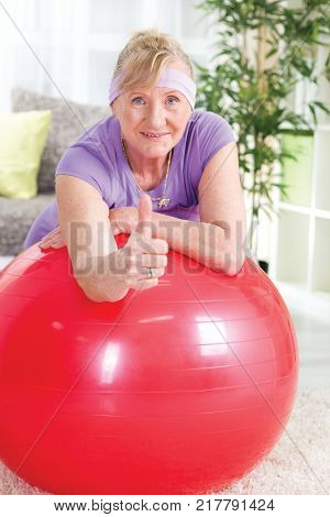 Senior woman after exercises shoving thumb up