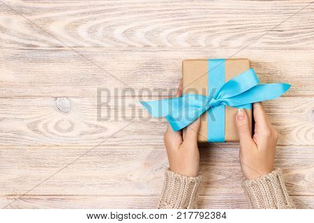 Woman hands give wrapped valentine or other holiday handmade present in paper with blue ribbon. Present box decoration of gift on white wooden table top view with copy space.