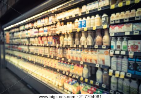Blurred Selection Of Dairy Products In Open Front Cold Fridge