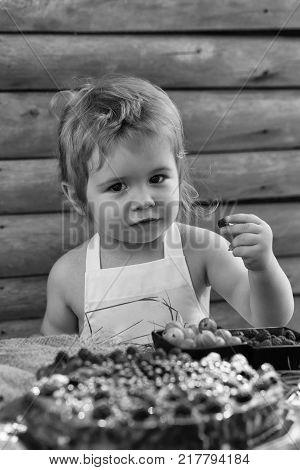 Cute little boy with blond hair in white pinafore eats red raspberry at rustic table with berries and fruit cake on wooden background