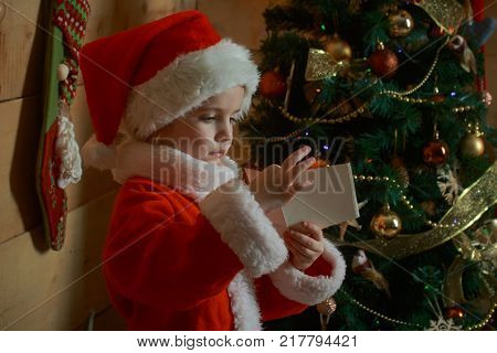 Christmas happy child read wish letter. Santa claus kid at Christmas tree. Xmas party celebration. Winter holiday and vacation. New year small girl with paper.