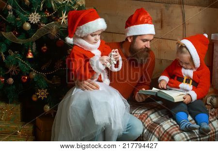 New year small girl and man fairytale. Santa claus kid and bearded man at Christmas tree. Winter holiday and vacation. Xmas celebration fathers day. Christmas happy children and father read book.
