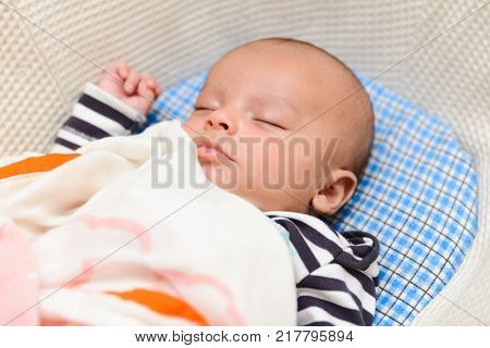 Eurasian baby sleeping in his cradle
