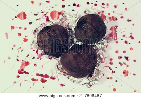 Baked beets on a white background with stains. Baking with aluminium foil. Baked beets for a Christmas soup. Holiday food