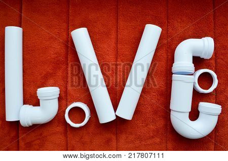 The inscription love is made up of white plumbing plastic pipes fittings flanges rubber gaskets on the background of a red carpet. A word of love written by water pipes.