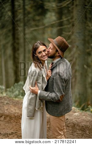 Bride and groom stand on forest road, embrace and laught in Carpathian mountains.
