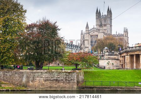 Bath United Kingdom - November 3 2017: River Avon landscape with The Abbey Church of Saint Peter and Saint Paul Bath commonly known as Bath Abbey. Ordinary people rest in Gardens Bath