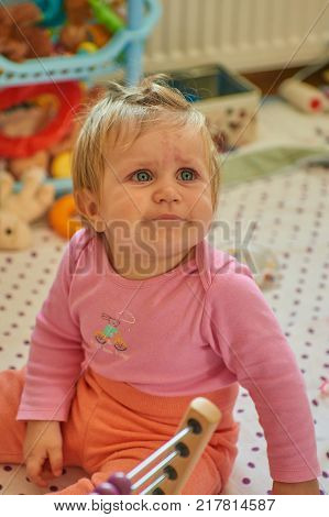 Baby girl blonde in children's room smile and looking away
