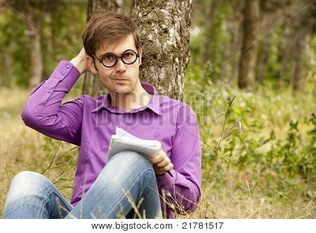 Funny men with glasses doing homework at the park.