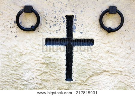 Old stone memorial cross at cemetery. Religious Christian symbol on white wall background