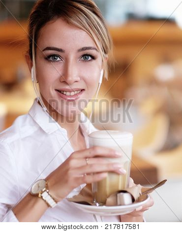 Beautiful blond woman smiling while listening to music with  hea