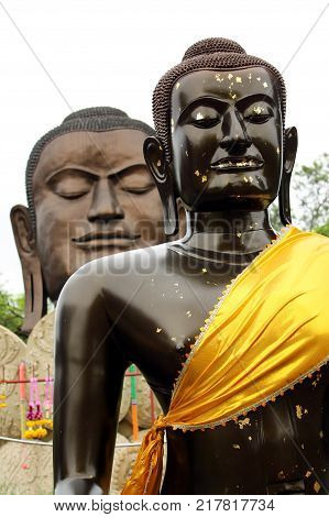 Dark Brown Budha statue with another Budha looking over his shoulder.