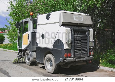 Machine sweeper - cleaner cleans the roadway. Machine brushes sweeping the street. The car vacuumed on the street. Municipal equipment.