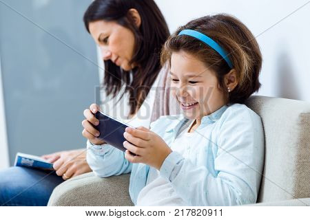 Mother And Daughter Using Mobile Phone In The Waiting Room Of The Doctor.