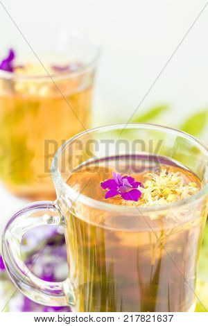 Linden Flower Tea In A Transparent Grog Glass With A Linden Blossom On The White Wooden Surface