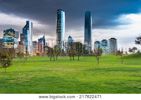 Meadows at Parque Bicentenario (Bicentennial Park) in the wealthy Vitacura district and skyline of buildings at financial district Santiago de Chile