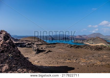 Beautiful barren Galapagos landscape view of Bartolome Island with unusual volcnic rock formations and blue sky