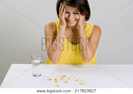 A beautiful adult woman sprinkled fish oil omega-3 tablets, and laughs. Vitamin D, E, A Fish Oil Capsules. Diet. Nutrition. Healthy Eating, Lifestyle.