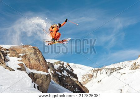 A professional skier makes a jump-drop from a high cliff against the blue sky leaving a trail of snow powder in the mountains. Photo from the slopes of Mount Elbrus. The concept of extreme sports and recreation in the mountains in winter. Copy the space.