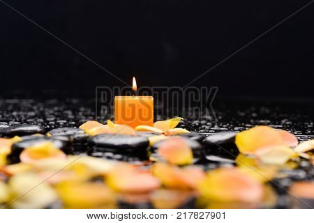 Yellow candle , rose petals and therapy stones